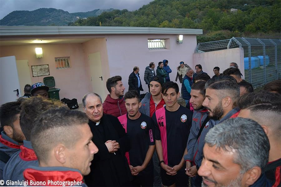 Il Parroco Don Pino Esposito prega insieme ai giovani calciatori il giorno dell'inaugurazione del campo sportivo